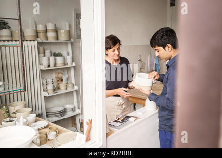 Potter showing product to customer - Stock Image