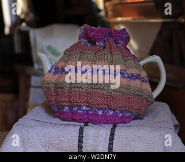 A hand knitted tea cosy in Brown, orange, green and purple shades of yarn that is on a large tea pot.  The tea cosy has a draw string around the top. - Stock Image