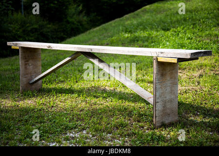 A wooden bench on a meadow - Stock Image