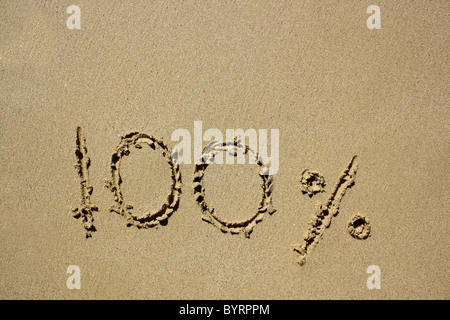 '100%' written out in wet sand. Please see my collection for more similar photos. - Stock Image