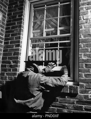 1950s THIEF MAN WEARING HAT GLOVES JACKET BREAKING INTO BRICK HOUSE OPENING WINDOW NIGHTTIME - c6207 HAR001 HARS MALES RISK ROBBER STEALING B&W WINDOWS THIEF ROBBERY DISASTER PROTECTION EXTERIOR LOW ANGLE OPPORTUNITY OCCUPATIONS BURGLARY CONCEPTUAL BREAK IN BREAKING AND ENTERING FELONY ILLEGAL MID-ADULT MID-ADULT MAN NIGHTTIME BLACK AND WHITE CAUCASIAN ETHNICITY HAR001 OLD FASHIONED THEFT - Stock Image