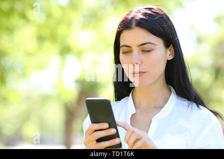 Serious beauty woman using smart phone standing in a park - Stock Image