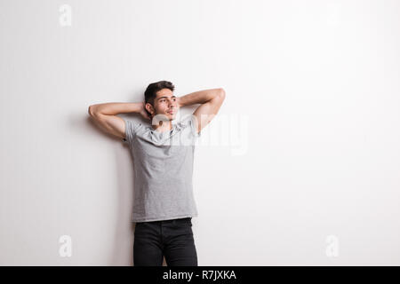 A cheerful young hispanic man standing in a studio, hands behind head. Copy space. - Stock Image