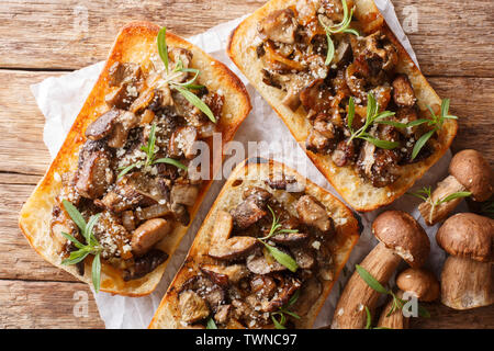 Delicious ciabatta with fried porcini mushrooms, onions, thyme and parmesan cheese closeup on the table. horizontal top view from above - Stock Image