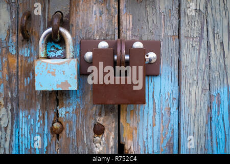two locks on old vintage wooden garage door, peeling paint - Stock Image