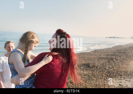 Lesbian couple and daughter on sunny beach - Stock Image
