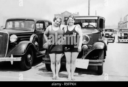 Two plump sisters pose in front of their car in the parking lot of Coney Island,ca. 1932. - Stock Image