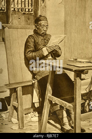 Elderly man reading at a table, Shanghai, China, East Asia. - Stock Image