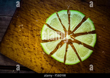 Sliced lime wheel on an old chopping board, rests on an old wooden table. - Stock Image
