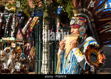A busker in traditional costume playing panpipes in Crewe town centre UK - Stock Image
