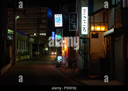 Night shot of empty street in Aomori, Japan, with car headlights at the end of the road and Japanese neon banners as the only light source. - Stock Image