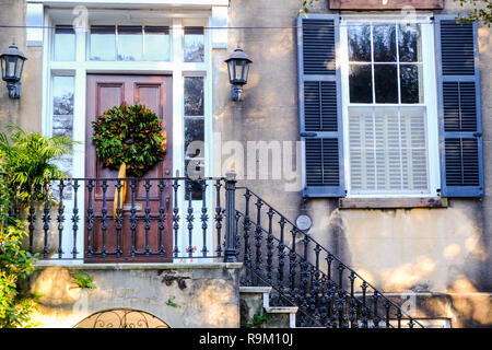 A traditionally southern Magnolia leaf Christmas holiday wreath decorate a wooden door on a historic home during the holidays on Lagare Street in Charleston, South Carolina. - Stock Image