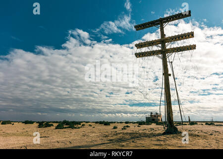 Abandoned powerline pole with disconnected and tangled wires in a former military test base on the Salton Sea in California. - Stock Image