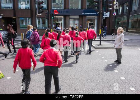 School children crossing Borough High Street in Southwark, London, SE1, UK - Stock Image