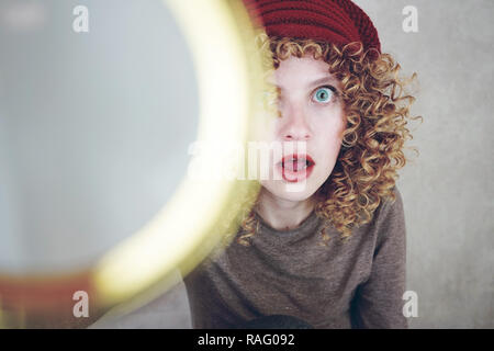 Close-up portrait of a beautiful and young funny woman with blue eyes and curly blonde hair investigating with a magnifying glass and she is surprised - Stock Image