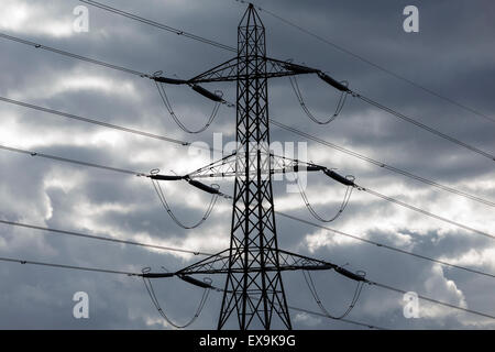 UK lattice pylon silhouetted against dark, brooding sky. - Stock Image
