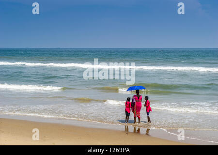 A mother and two daughters enjoy the sea at Marina Beach, with the Bay of Bengal in Chennai, India - Stock Image