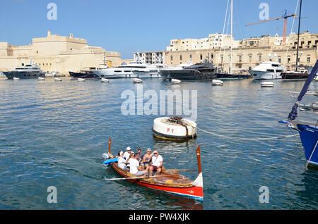 A traditional dghasja painted water taxi and other boats on the Grand harbour in the Three Cities area of Malta - Stock Image