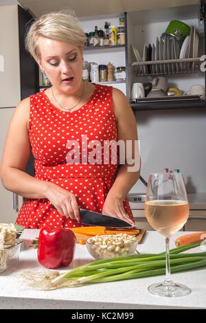 Female cutting carrot and preparing for vegetable wok - Stock Image