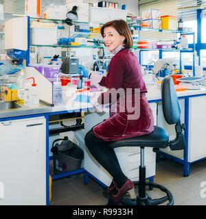 Smiling young chemist in chemistry research lab dressed as if she were going to a nightclub - Stock Image