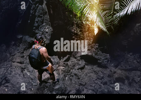 Man climber stands near cave's exit or big rock in darkness - Stock Image