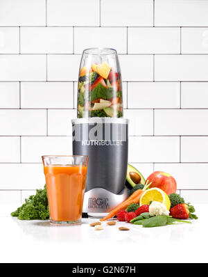 A Nutribullet in a kitchen environment surrounded by healthy fruit and vegetables. - Stock Image