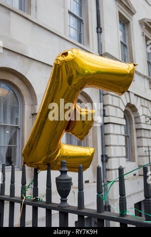 An E balloon (representing the concept of remaining in Europe) blows in the wind on railings during a pro-EU brexit protest opposite Parliament, on 11th March 2019, in Westminster, London, England. - Stock Image