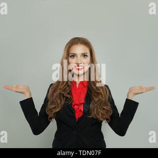Successful woman holding two empty open hand on white background. Rate, weigh and represent - Stock Image