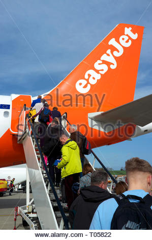 Passengers ascend the steps to board an Easyjet flight at Bristol Airport, Lulsgate, Bristol, UK. - Stock Image