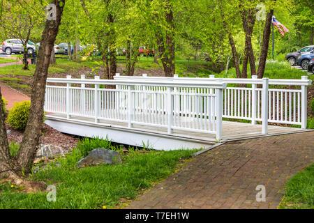 JONESBOROUGH, TN, USA-4/28/19: An elegant white footbridge crossing a dry creek in Jimmy Neil Smith park. - Stock Image