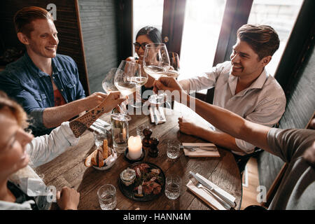 Group of men and women enjoying wine at restaurant. Young friends toasting wine at cafe. - Stock Image