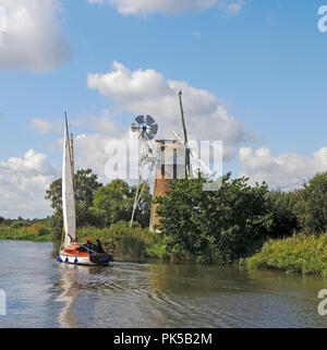 A yacht sailing by Turf Fen Drainage Mill on the River Ant on the Norfolk Broads opposite How Hill, Ludham, Norfolk, England, United Kingdom, Europe. - Stock Image