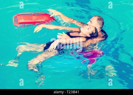 Lifeguard rescuing young woman. Toned image. - Stock Image