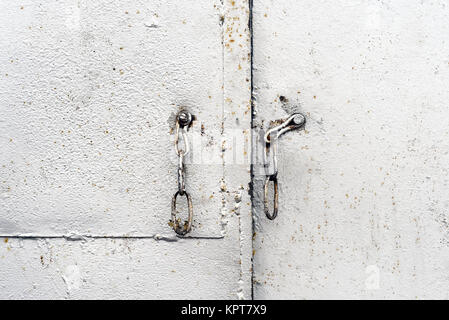 An unlocked rusty vintage chain with a silver metal painted background garage entrance door - Stock Image