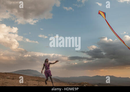 Maasai Warrior learning to fly a kite. Kenya, Africa. - Stock Image