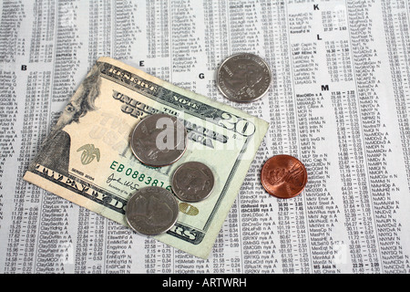 Twenty dollar bill and coins on stock financial page - Stock Image