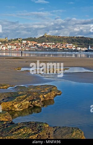Scarborough's castle headland against the sand and rockpools of South Bay beach at low tide. - Stock Image