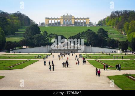 Vienna tourism, view of tourists walking through the formal gardens of the Schloss Schönbrunn palace in Vienna, Austria. - Stock Image