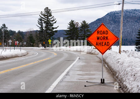 A road work ahead sign in snow covered Speculator, NY USA - Stock Image