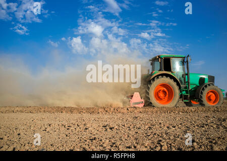 Farm tractor preparing dusty soil affected by drought. Drought and agriculture concept - Stock Image