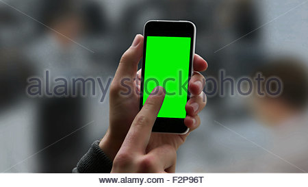 Chroma key screen smart phone touch screen. Male hand holding phone and touching the screen, copy space for your - Stock Image
