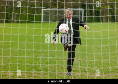 Former England footballer Trevor Brooking  international West Ham MBE kicking a football towards a net like taking  penalty kick. - Stock Image
