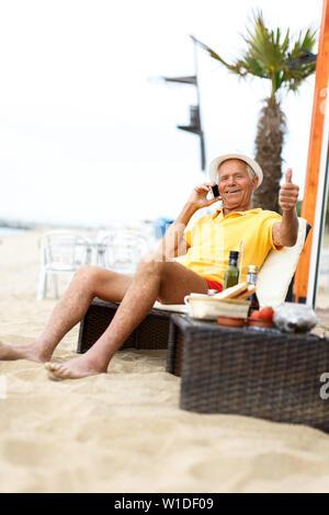 Ordinary mature man sitting and speaking phone near ocean - Stock Image