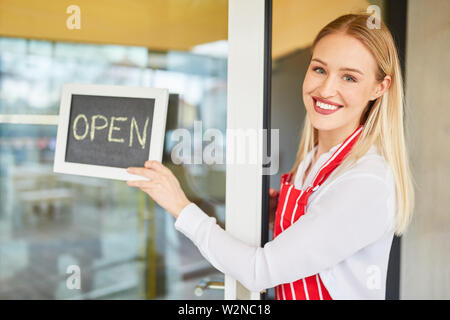 Young woman at the opening of her restaurant or bistro with chalkboard - Stock Image
