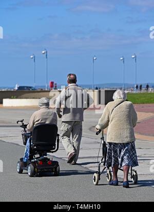 Three elderly people walking on The Promenade, Morecambe, Lancashire, England, United Kingdom, Europe. - Stock Image