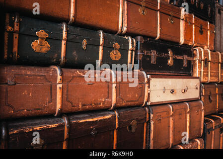 Old vintage suitcases standing in a stack. Vintage background - Stock Image