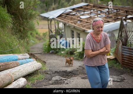 A Puerto Rican resident walks by damaged homes in the aftermath of Hurricane Maria October 29, 2017 in Utuado, Puerto - Stock Image