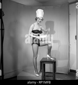 Model seen here in a chef hats making pancake mix, Tuesday 1st March 1960. - Stock Image