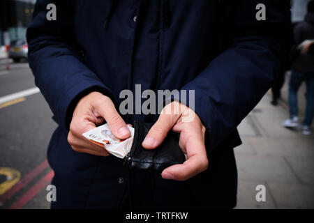 closeup of a young caucasian man on the street putting in or taking off some pound sterling banknotes from his wallet - Stock Image