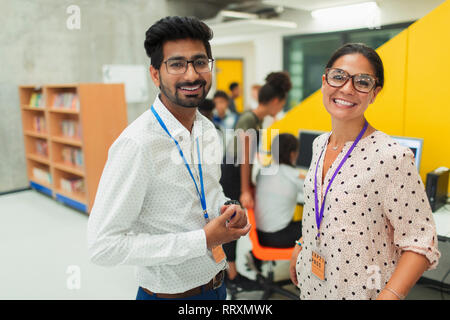 Portrait smiling, confident junior high teachers in library - Stock Image